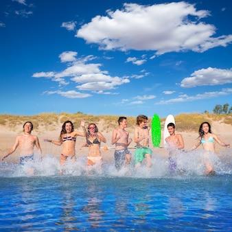 Grupo de surfistas adolescentes correndo praia espirrando