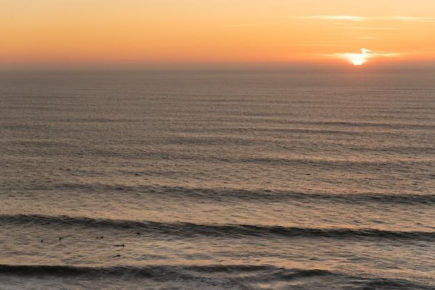 Grupo de surfistas esperando por uma onda no meio do mar com o sol ao entardecer no fundo