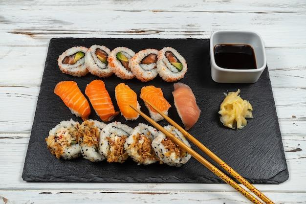 Grupo de sushi fresco com pauzinhos de madeira