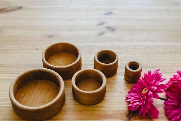 Grupo de tigelas de madeira redondas e vazias e flores roxas com espaço livre para texto