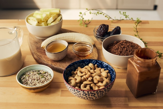 Grupo de tigelas e potes com ingredientes para smoothie