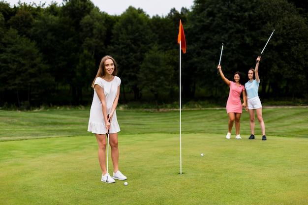 Grupo de tiro completo de meninas jogando golfe