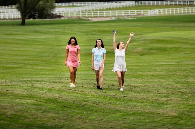 Grupo de tiro completo de mulheres no campo de golfe