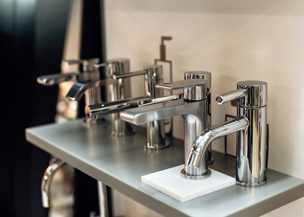 Grupo de torneiras de água elegantes e modernas para banheiro em showroom linhas de torneiras novas em oficina de encanamento