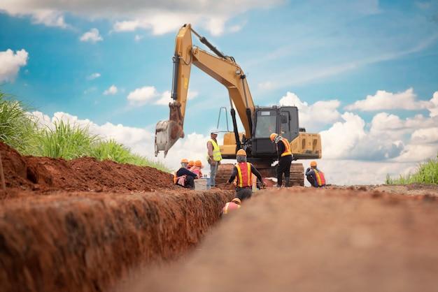 Grupo, de, trabalhador, e, engenheiro construção, desgaste, segurança, uniforme, escavação, drenagem água