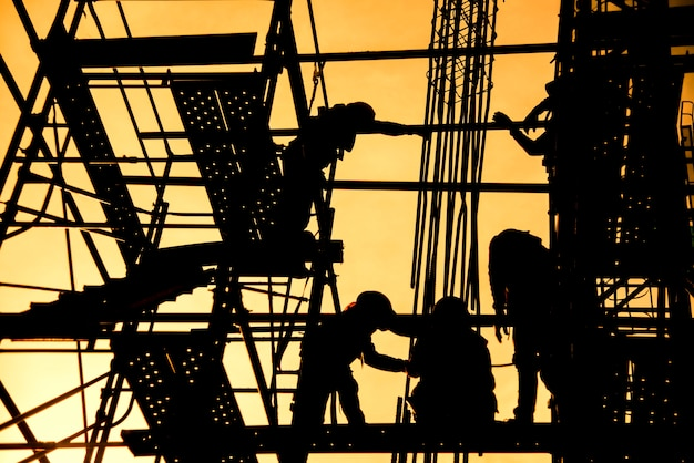 Grupo de trabalhador em uniforme de segurança instalar coluna de aço reforçada em construção