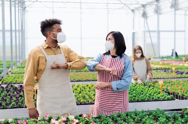Grupo de trabalhadores cumprimentando em estufa no centro do jardim, o conceito de coronavírus.