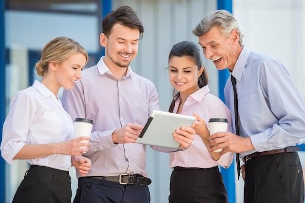 Grupo de trabalhadores de escritório bem sucedido que têm a ruptura de café.