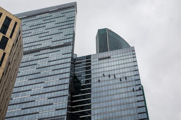 Grupo de trabalhadores de limpeza de janelas no prédio alto