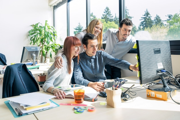 Grupo de trabalhadores empregados jovens com computador no escritório urbano alternativo