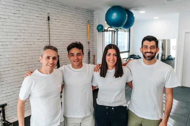 Grupo de trabalhadores latinos e caucasianos, nutricionista, personal trainer, fisioterapeuta e recepcionista tirando um retrato após ajudar seus clientes