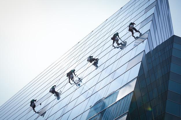 Grupo de trabalhadores, limpeza de janelas de serviço em prédio alto