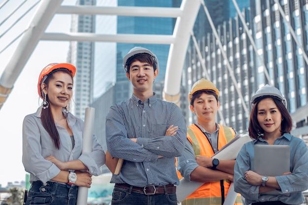 Grupo de trabalhadores profissionais de engenheiros, empresários, trabalho em equipe de engenheiros em pé com o fundo da cidade.