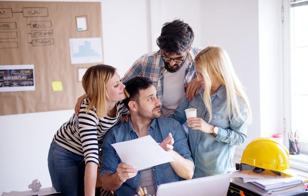 Grupo de trabalhadores sorridentes alegres em pé ao redor de seu chefe e falando sobre o plano de negócios no escritório.