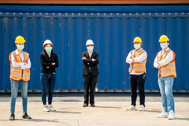 Grupo de trabalhadores usa máscaras faciais de proteção e capacetes de segurança em canteiro de obras com distância social