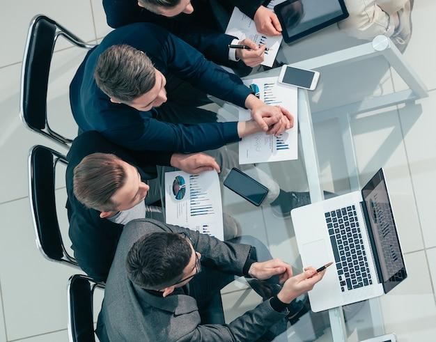 Grupo de trabalho da vista superior discutindo o plano de negócios financeiro
