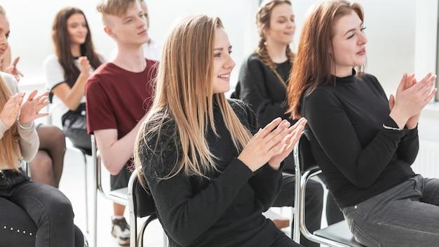 Grupo de trabalho de jovens profissionais sentados na sala de conferências. foto com espaço de cópia