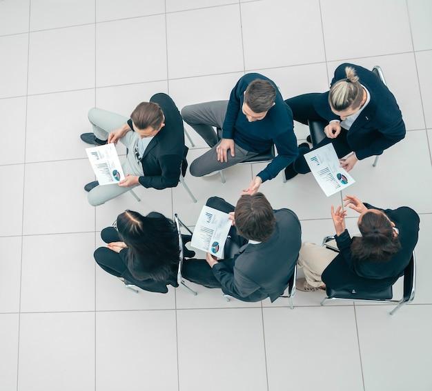 Grupo de trabalho de visão superior com gráficos financeiros em uma reunião conjunta