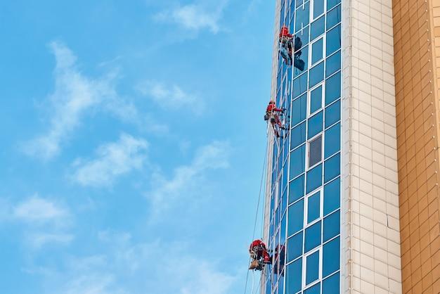Grupo de trabalho industrial alpinista em um edifício moderno ao ar livre