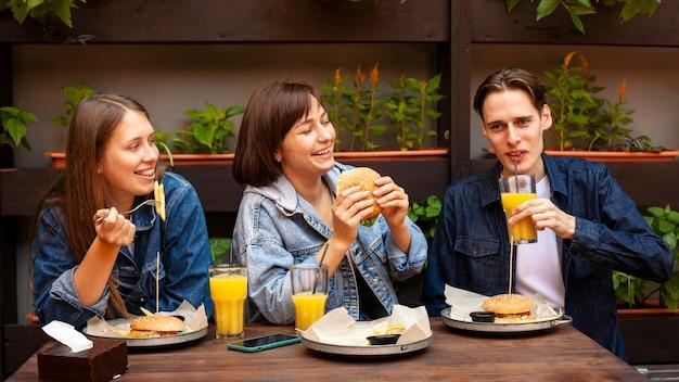 Grupo de três amigos comendo hambúrgueres