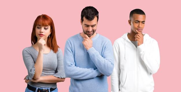 Grupo de três amigos de pé e olhando para baixo