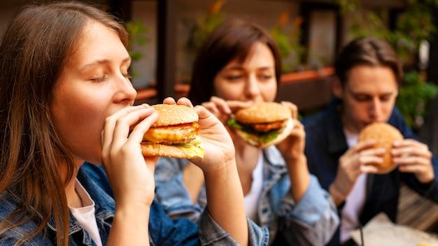 Grupo de três amigos degustando hambúrgueres