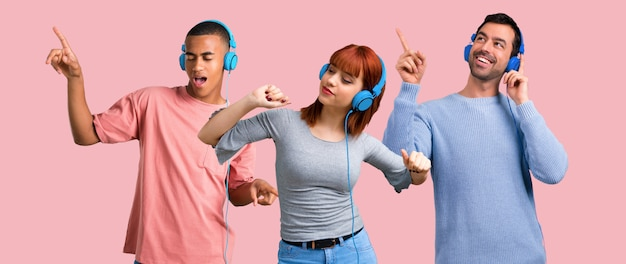 Grupo de três amigos ouvindo música com fones de ouvido