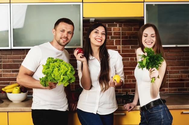 Grupo de três amigos preparando comida para o jantar, posando na cozinha segurando frutas e legumes. promovendo uma alimentação saudável. amigos estão preparando uma salada