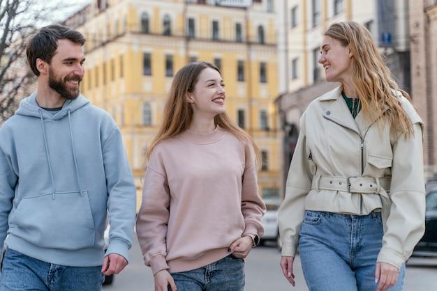 Grupo de três amigos sorridentes ao ar livre na cidade