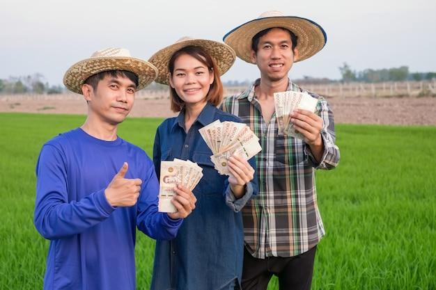 Grupo de três fazendeiros asiáticos segurando notas tailandesas e levante a mão em pé na fazenda de arroz