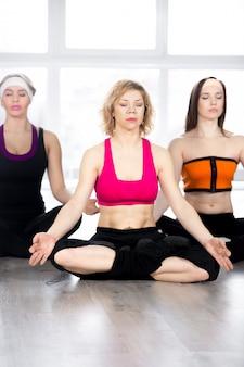 Grupo de três fêmeas sentadas de pernas cruzadas em meditação em sala de aula