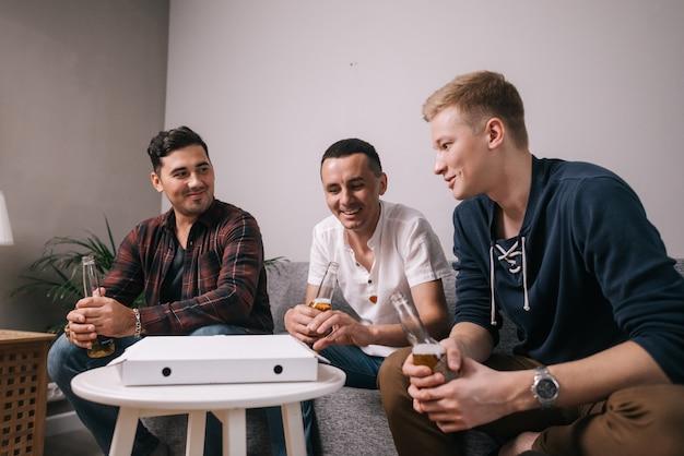 Grupo de três jovens amigos comendo pizza em casa