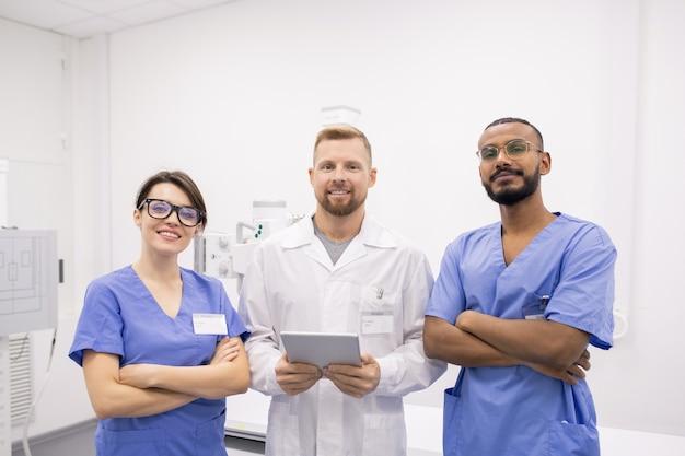 Grupo de três jovens clínicos interculturais de sucesso ou estagiários de uniforme em frente à câmera no hospital