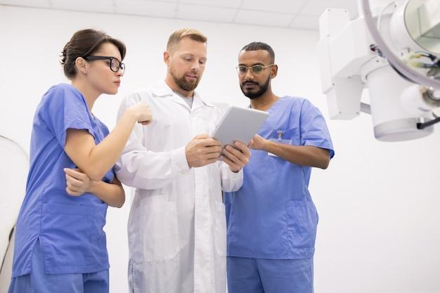 Grupo de três jovens médicos uniformizados, consultando sobre peculiaridades de novos equipamentos médicos durante o uso de tablet