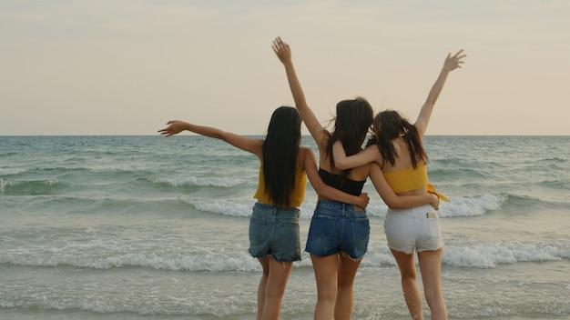 Grupo de três jovens mulheres asiáticas caminhando na praia