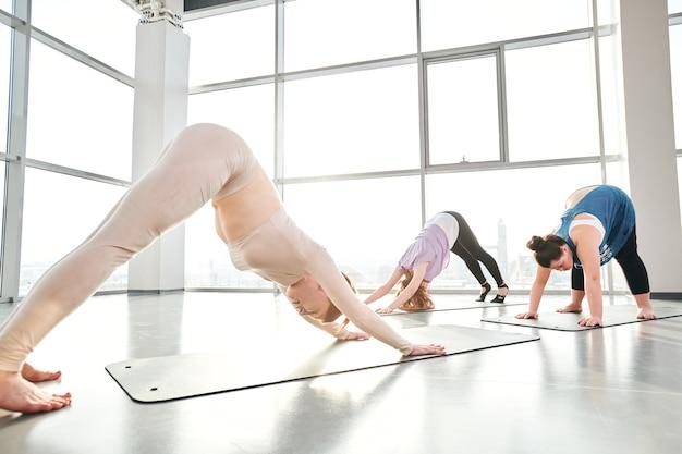 Grupo de três jovens mulheres ativas em roupas esportivas, inclinando-se para a frente, com os braços e as pernas esticados enquanto estão de pé nos tapetes