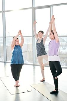 Grupo de três jovens mulheres ativas fazendo exercícios de ioga em pé sobre esteiras durante o treino esportivo na academia