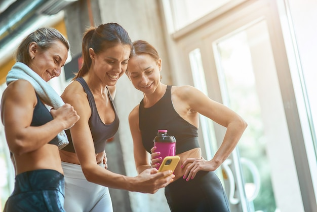 Grupo de três jovens mulheres bonitas e felizes e esportivas tirando selfie no smartphone enquanto descansam