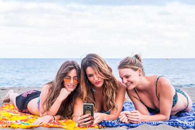 Grupo de três lindas garotas em amizade fica deitado relaxado na praia falando e usando um smartphone para compartilhar seu estilo de vida de verão com os amigos em casa