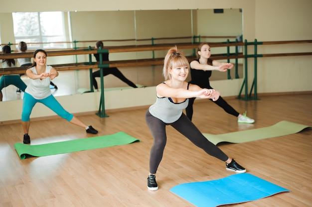 Grupo de três meninas fazendo exercícios na academia