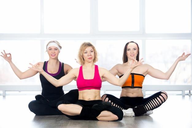 Grupo de três mulheres praticam yoga em sala de aula