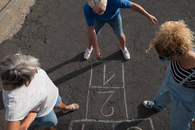 Grupo de três pessoas brincando juntos na rua, no asfalto, na amarelinha - idosos ativos e mulher se divertindo