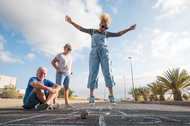 Grupo de três pessoas caucasianos se divertindo e brincando de amarelinha juntos - linda mulher pulando no meio do asfalto e dois idosos olhando para ela