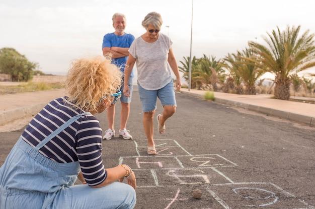 Grupo de três pessoas como adultos e idosos - dois idosos brincando de amarelinha com uma mulher encaracolada olhando para a mulher madura pulando
