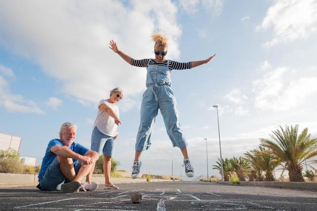 Grupo de três pessoas se divertindo na rua brincando na amarelinha - dois idosos e uma linda mulher pulando