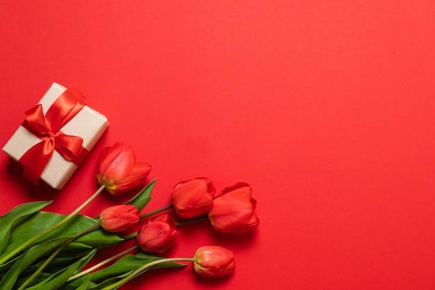 Grupo de tulipas e de caixas de presente vermelhas com fitas vermelhas em um fundo vermelho.