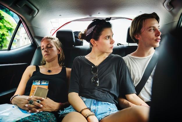 Grupo de turista sentado no banco de trás de táxi, fazendo passeios turísticos