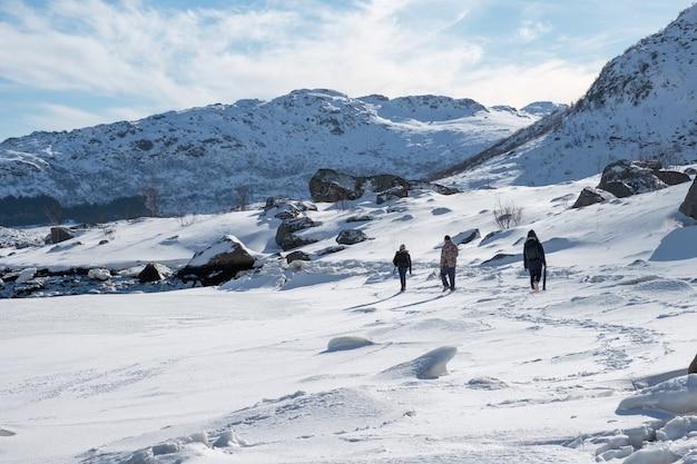 Grupo de turistas caminhando em uma colina de neve em nordland em um dia ensolarado