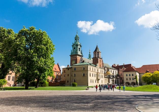 Grupo de turistas caminhando no castelo de wawel, cracóvia, polônia. cidade europeia com edifícios de arquitetura antiga, lugar famoso para viagens e turismo