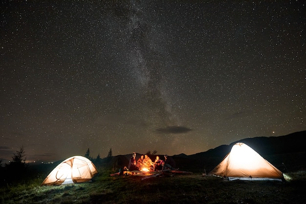 Grupo de turistas com guitarra queimando uma fogueira sob o céu escuro estrelado com a constelação da via láctea.
